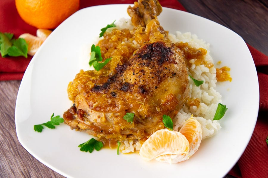 braised chicken with orange sauce on a white plate over rice with chopped parsley