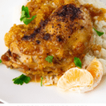 A chicken thigh with mandarin orange sauce on a white plate with rice