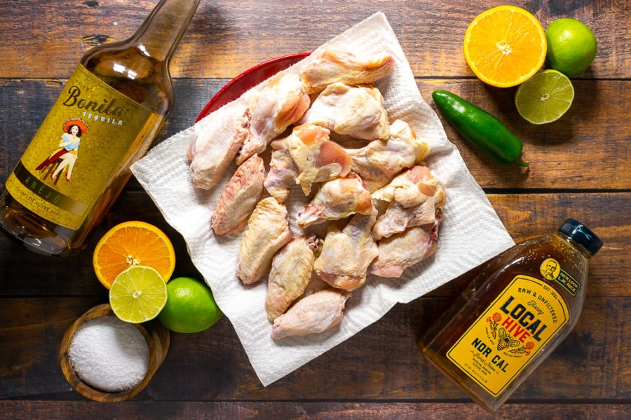 a plate of chicken wings, an orange sliced in half, a jalapeno, three limes with one sliced in half, a bowl of salt, bottle of honey, and a bottle of tequila