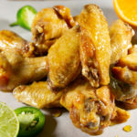 tequila lime chicken wings on a parchment sheet with sliced limes and oranges