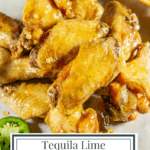 fried chicken wings in tequila lime sauce piled on parchment paper near sliced citrus