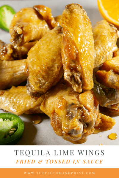 a pile of deep fried wings in a sticky tequila lime sauce on a piece of parchment paper