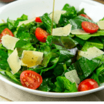 a bowl of tomato spinach salad with parmesan on a beige towel