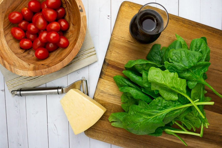 a wooden cutting board with fresh spinach, a wedge of parmesan cheese, a vegetable peeler, a wooden bowl of cherry tomatoes and a carafe of dressing