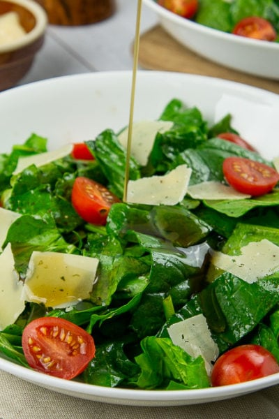 a bowl of tomato spinach salad with a vinaigrette being drizzled on top