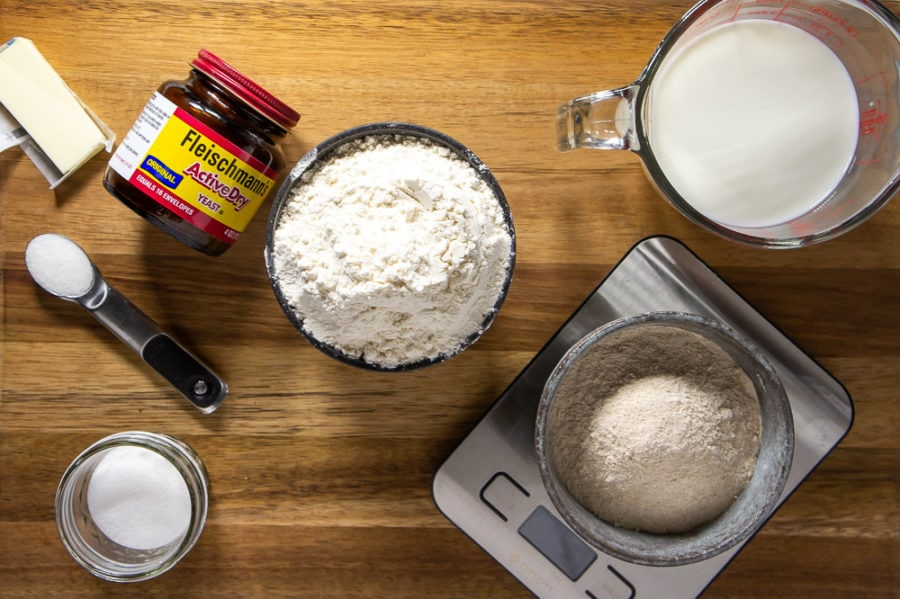 a bowl of flour, a bowl of yeast, a cup of milk and sugar on a wooden cutting board
