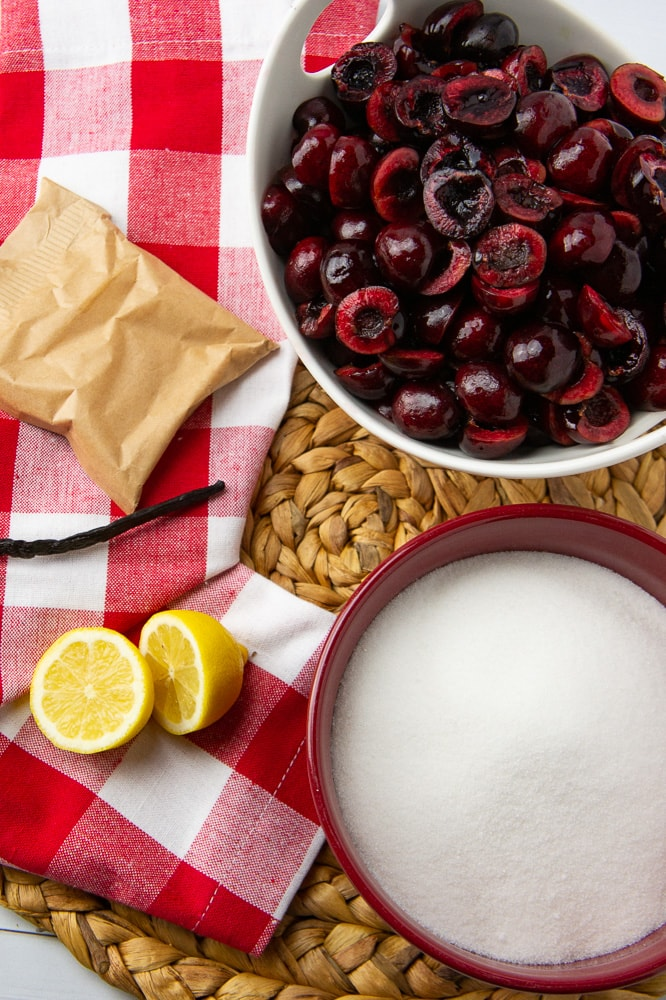 a bowl of pitted fresh cherries, a bowl of sugar, a halved lemon a vanilla bean and a pectin packet on a red checked napkin