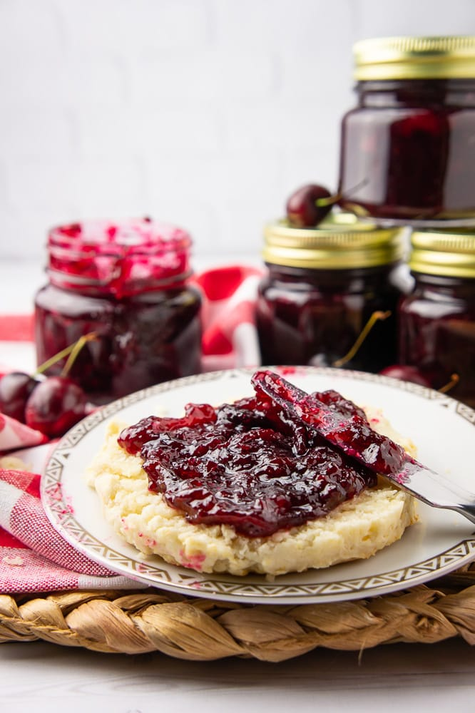 a biscuit with cherry vanilla jam spread on it in front of jam jars