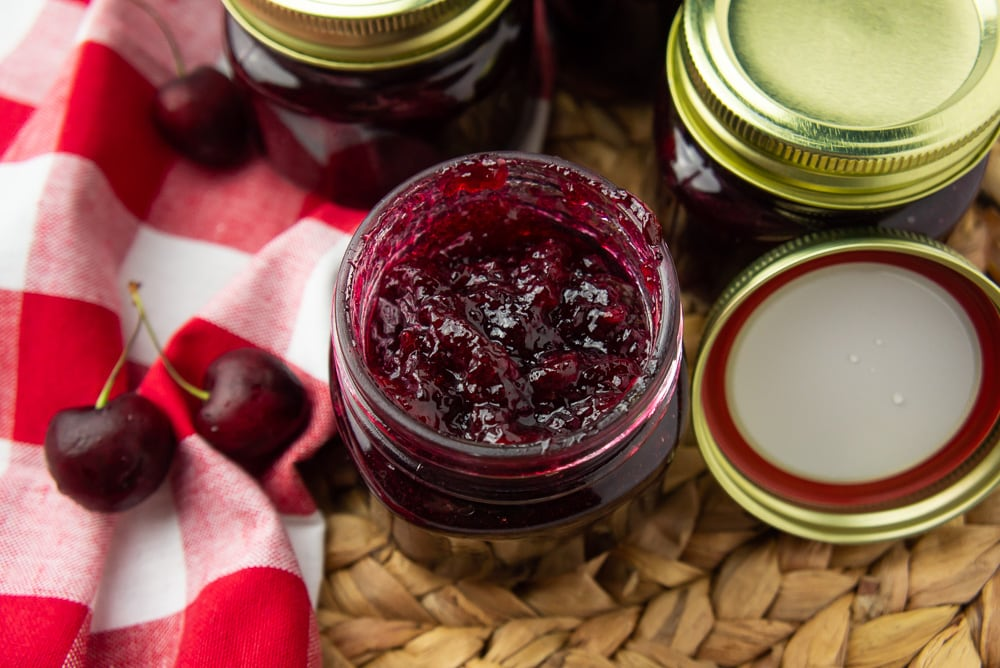 an open jar of cherry vanilla jam with a red checked napkin and fresh cherries beside it
