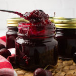 a jar of cherry vanilla jam with a spoon scooping some out