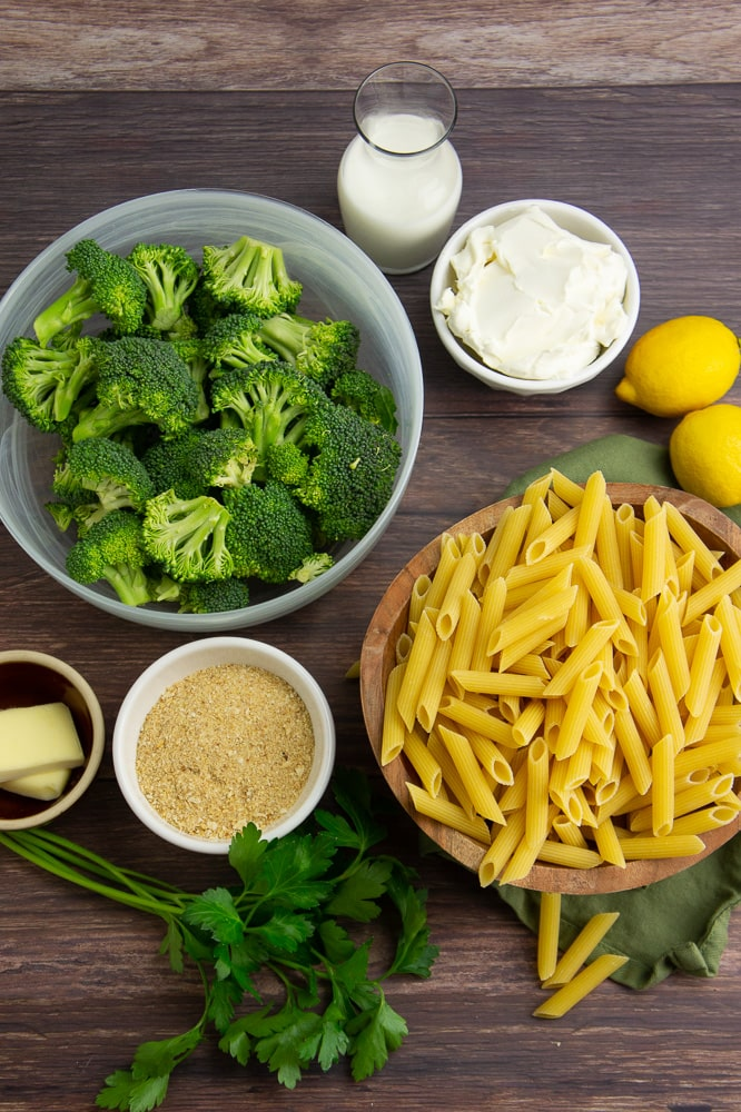 a bowl of penne next to a bowl of broccoli, with several small bowls of cream cheese, milk, breadcrumbs, and two lemons