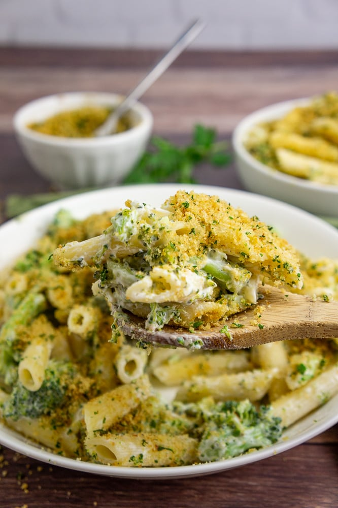 a large white bowl of lemon broccoli pasta with a wooden spoon lifting out a scoop