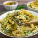 a white bowl of broccoli pasta with a wooden spoon lifting out a scoop