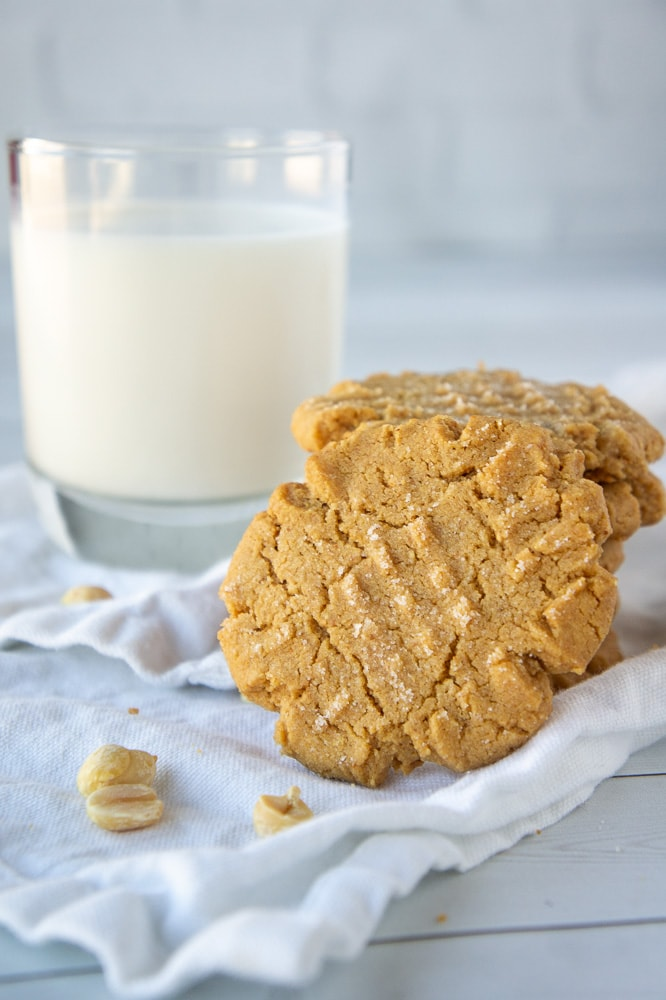 a stack of flourless peanut butter cookies in front of a glass of milk