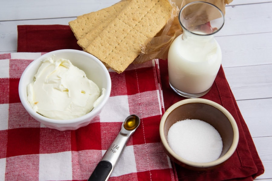 a bowl of cream cheese, a crafe of heavy cream, graham crackers, vanilla extract and sugar on a red napkin