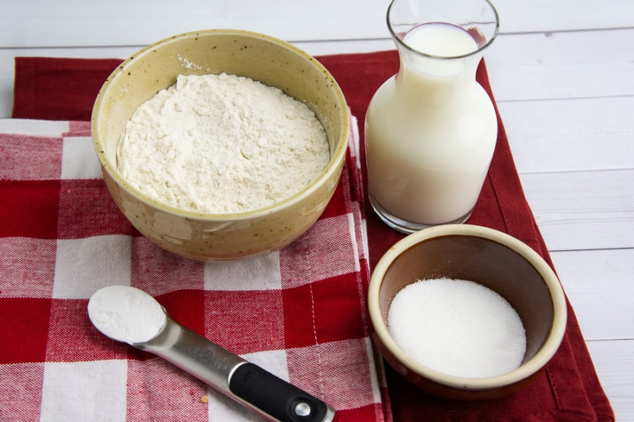 a bowl of flour, a bowl of sugar, a glass of milk and teaspoon of baking powder