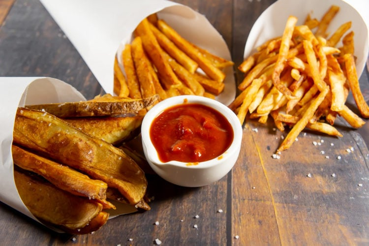 three cones of fries with ketchup on a wooden table