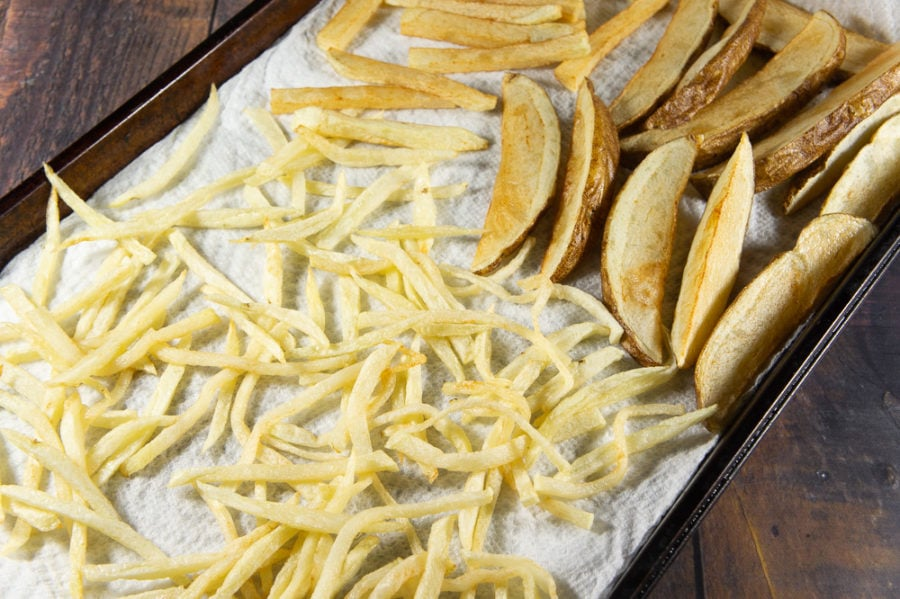 a sheet pan covered in paper towels and lightly blanched french fries