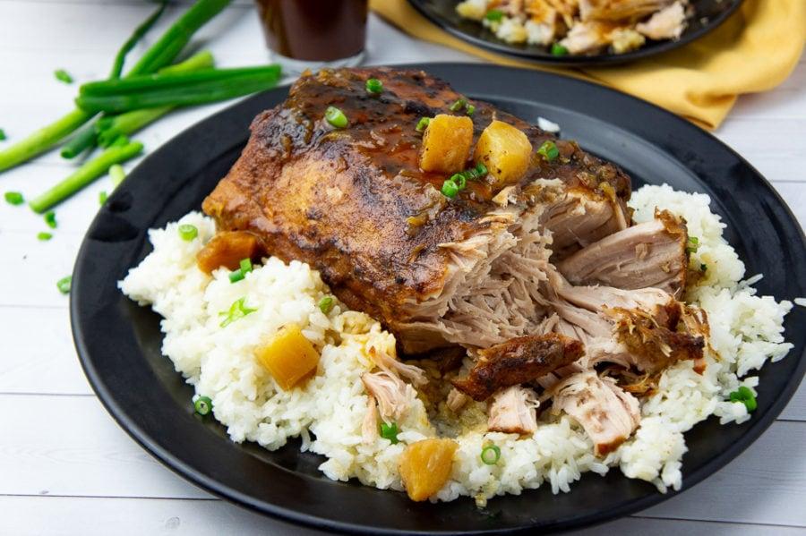 crockpot pineapple pork loin shredded on a platter with rice and sauce