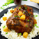 a black platter with rice and pineapple chunks around a roasted pork loin