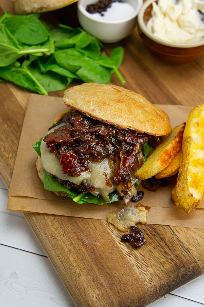 a burger with bacon onion jam next to french fries, fresh spinach, a small bowl of mayo and a small bowl of salt on a wooden cutting board