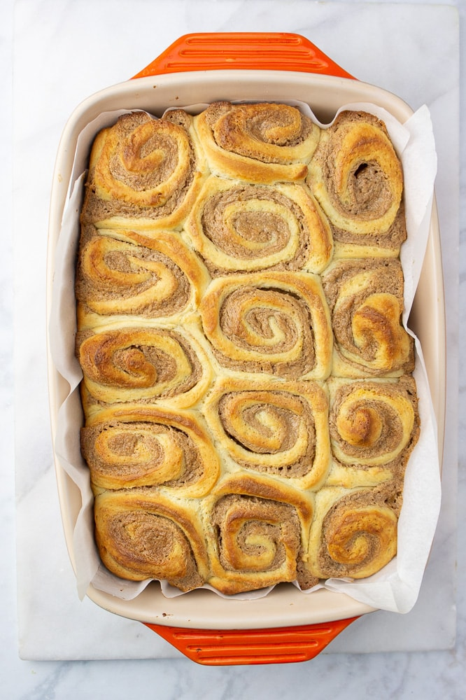 an orange baking dish of golden brown cinnamon rolls