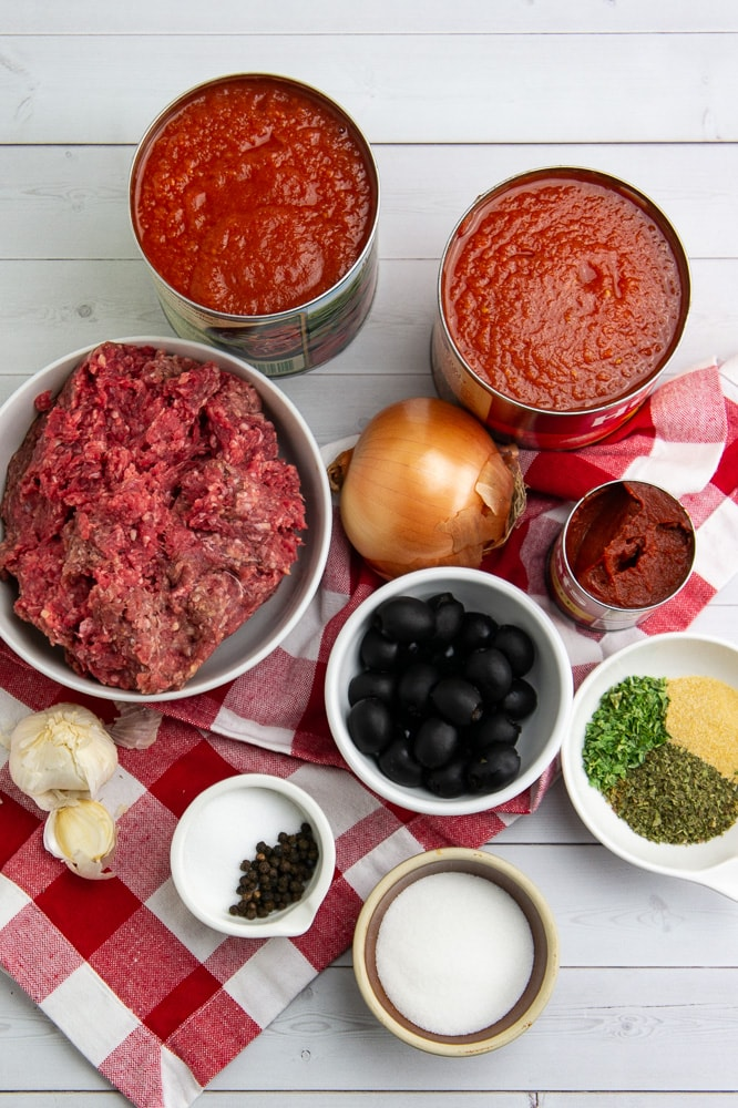 A bowl of ground beef, an onion, a bowl of olives, a bowl of dried herbs, a bowl of salt, and several cans of tomato sauce on a white wooden table