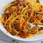 a white bowl of spaghetti noodles tossed with red sauce on a white wooden table