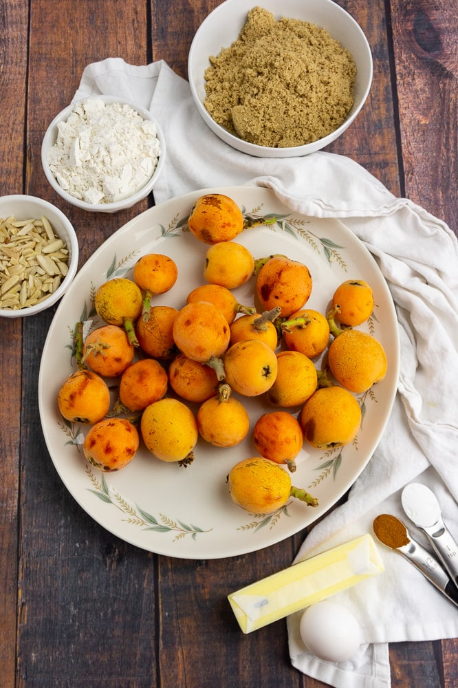 a white platter full of loquats with a bowl of brown sugar, a small bowl of almonds, a small bowl of flour, a stick of butter and a teaspoon of cinnamon on a white towel