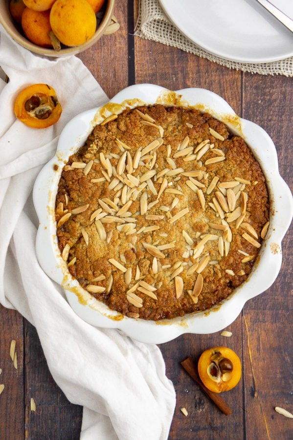 a white pie plate with loquat cobbler baked in it on a wooden table with a white dish towel and sliced raw loquats
