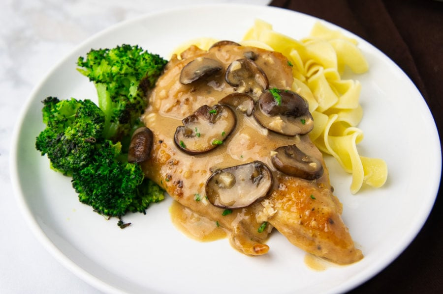 A cooked chicken breast in creamy mushroom marsala sauce on a white plate with egg noodles and broccoli