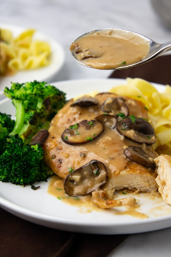 a white plate with chicken marsala, broccoli, and egg noodles on a brown napkin