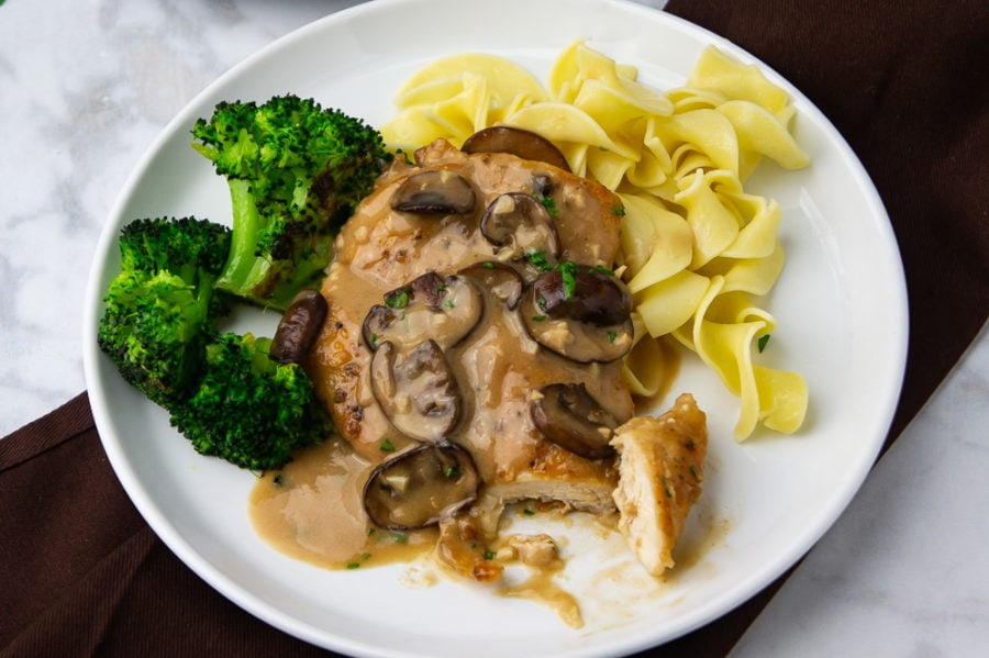 A white plate with a brown linen napkin, a chicken breast with marsala sauce over pasta and broccoli on the plate with one bite cut off.