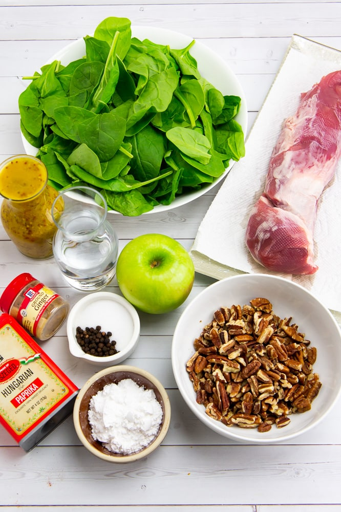 a bowl of spinach beside a carafe of yellow dressing, a carafe of water, a bowl of salt and pepper, a container of ginger and of paprika, a bowl of pecans, an apple, and a plate with a pork tenderloin on it