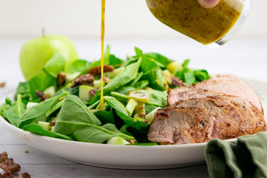 a white platter piled with spinach and a sliced pork tenderloin with an apple in the background and dressing being poured over the top