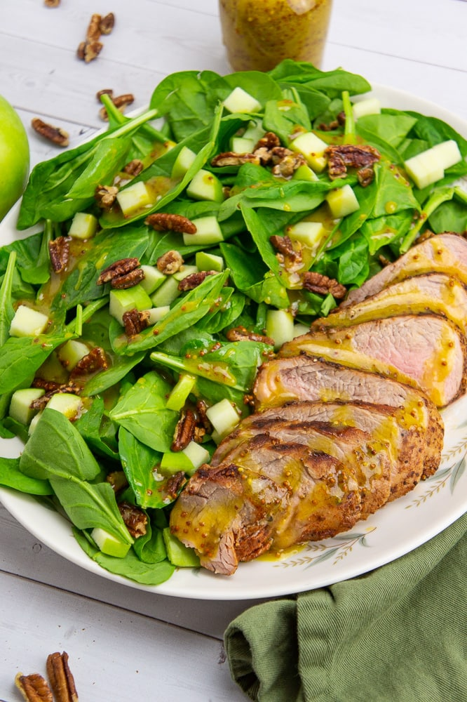 a large platter with a pork tenderloin sliced next to a spinach salad topped with dressing, pecans, and apples