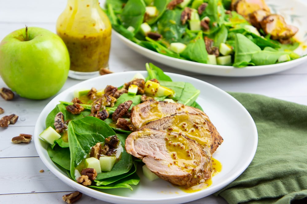 a small white plate with spinach, pecans, apples, and pork tenderloin on it drizzled with a yellow dressing in front of a carafe of the dressing and a large platter with the same salad.