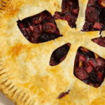 a cherry rhubarb pie beside fresh cherries and a white linen napkin