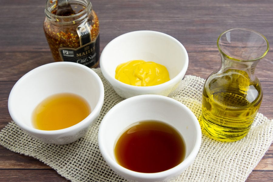 three white bowls with mustard and syrup in them, with a glass of oil and a jar of whole grain mustard