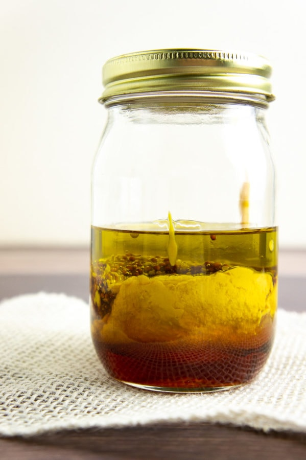 a mason jar with layers of salad dressing ingredients added in