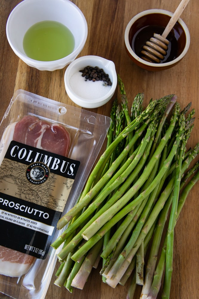 a pile of asparagus with a package of prosciutto, a bowl of honey, a bowl of oil, and salt and pepper on a wooden cutting board