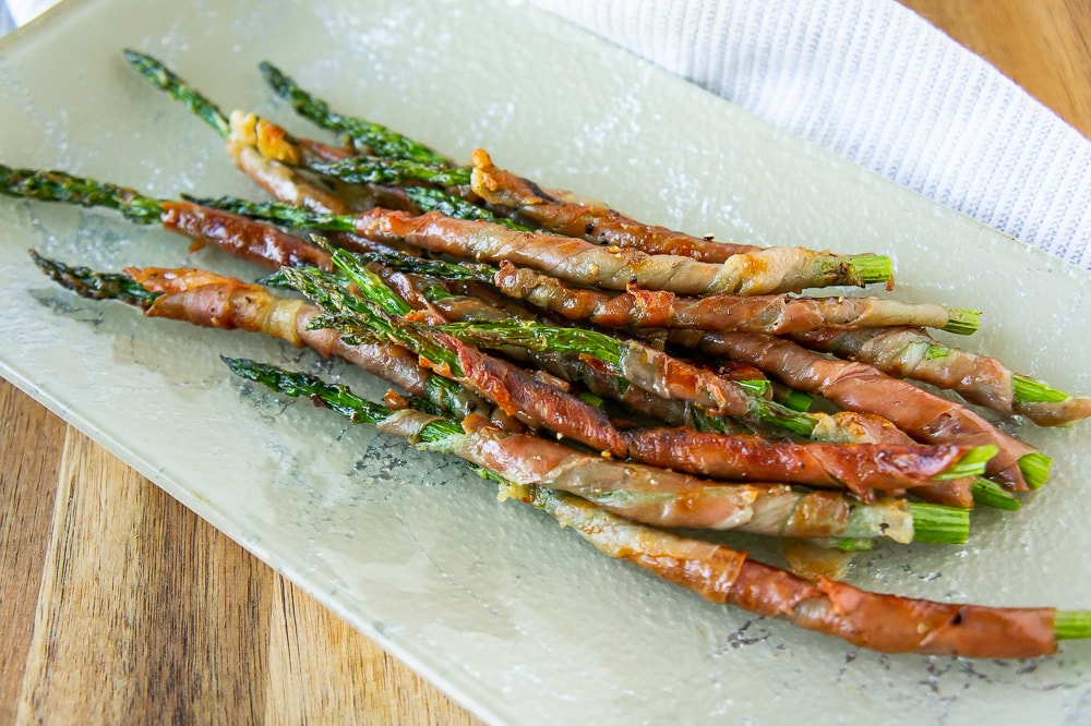 a platter of grilled prosciutto wrapped asparagus on a wooden cutting board