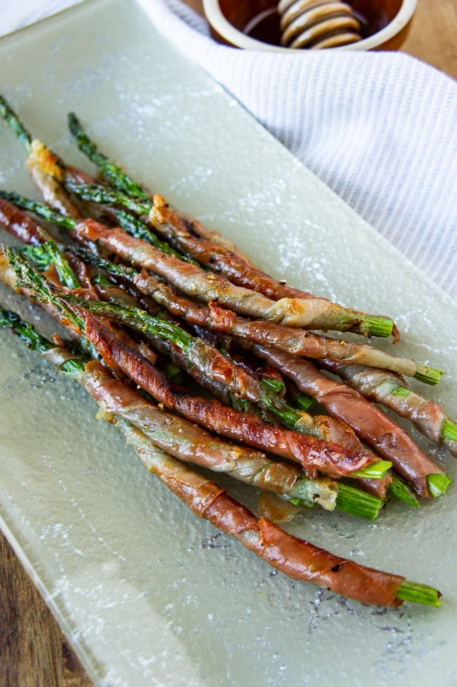 a platter of prosciutto wrapped asparagus with a wooden cutting board and white linen towel