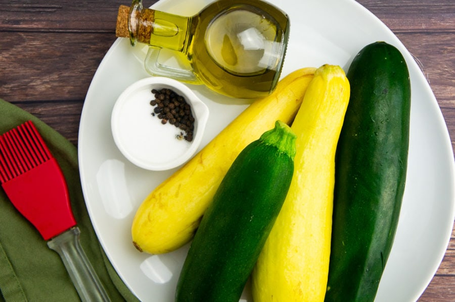 a white platter with a stack of summer squash, a small bowl of salt and pepper, a glass of olive oil, and a silicone brush