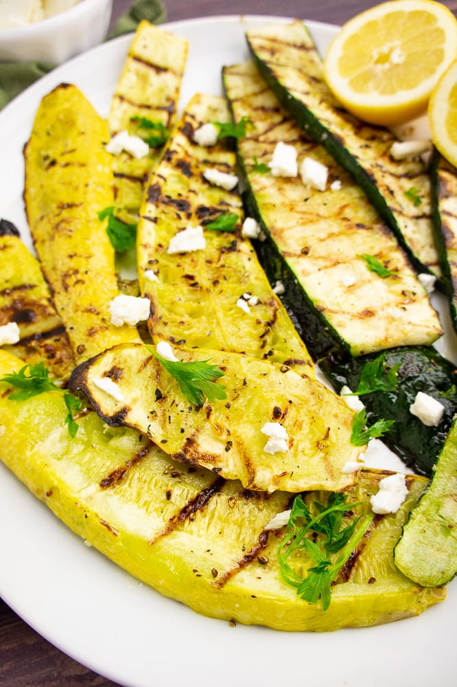 a white plate of grilled summer squash with a halved lemon and crumbled white cheese