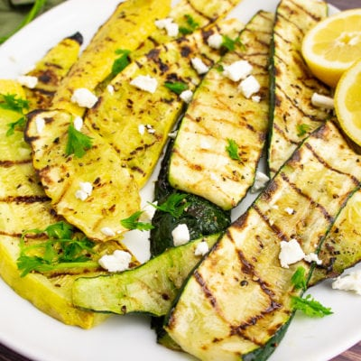 grilled summer squash on a white platter topped with feta and sunflower seeds.