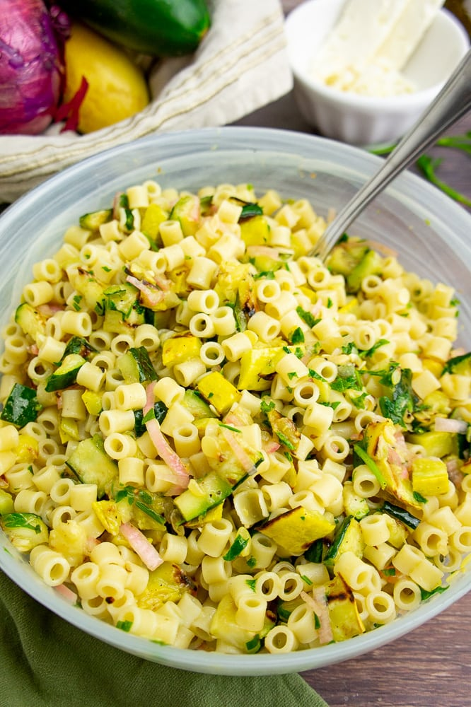 a large frosted bowl with summer squash pasta salad and a serving spoon on a brown wooden surface in front of a bowl of fresh vegetables.