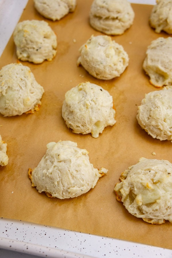 a baking sheet with brown parchment paper and baked drop biscuits