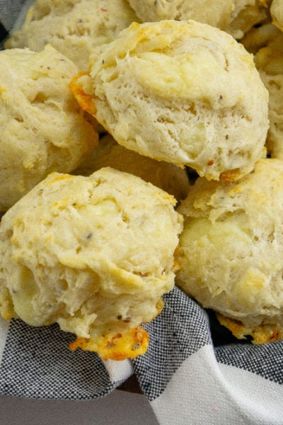 a black checkered napkin full of asiago biscuits