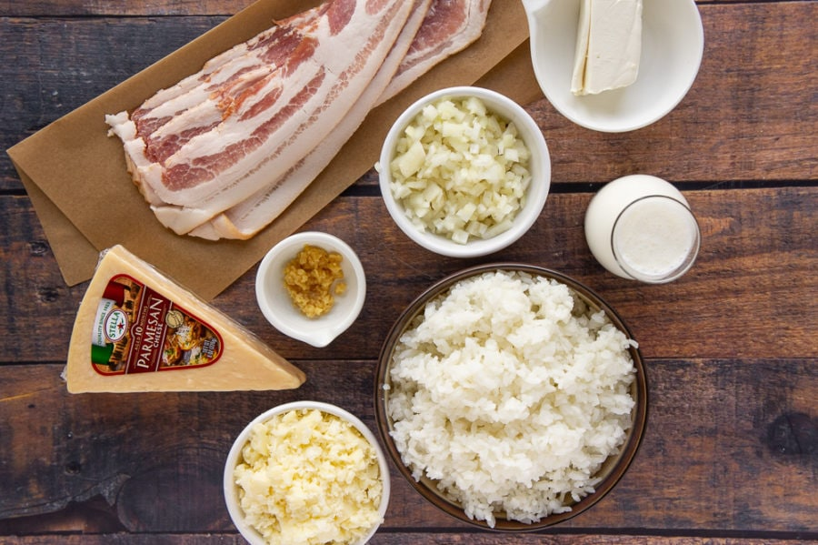 a wooden table with bacon slices on parchment paper, a bowl of rice, a bowl of chopped onion, a wedge of cheese and a carafe of cream